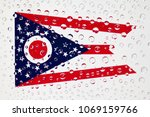 Small photo of Flag of American State Ohio behind a glass covered with raindrops. Patriots day, memorial weekend, veterans day, presidents day, independence day background.