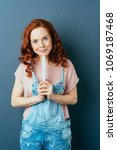 Small photo of Pretty pert young redhead woman in dungarees looking at the camera with a playful grin as she holds a builders ruler over a dark studio background