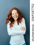 Small photo of Laughing young redhead woman screwing up her eyes in mirth as she poses with folded arms over a dark studio background