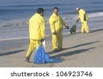 Small photo of CIRCA 1990 - Three oil cleanup workers cleaning up the beach with adsorbent material after an oil spill covered Huntington Beach, California