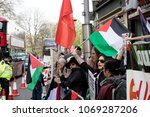 London, United Kingdom, 14th April 2018:- Protesters gather along Kensington High Street, near the Israeli Embassy in London to protest the ongoing occupation of Palestine. - stock photo