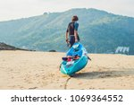 young man carrying his kayak... | Shutterstock . vector #1069364552