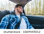 young man slipping in car at... | Shutterstock . vector #1069445012
