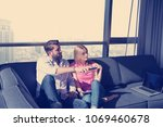 young couple sitting on sofa... | Shutterstock . vector #1069460678