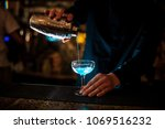 Barman In A Blue Shirt Pours...