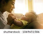 happy mother playing with her... | Shutterstock . vector #1069651586