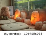 Small photo of seat in the middle of a lot Himalayan salt lamps and tealights closeup