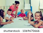 Small photo of Cheerful diligent kids learning to write on lesson in elementary school class