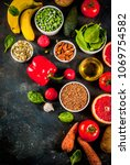 Small photo of Healthy food background, trendy Alkaline diet products - fruits, vegetables, cereals, nuts. oils, dark blue concrete background copy space top view