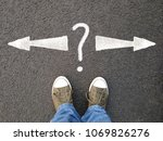 Small photo of feet in canvas shoes standing on asphalt from personal perspective, road markings with arrows pointing left and right with question mark