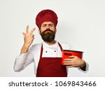man with beard holds red pot on ...   Shutterstock . vector #1069843466