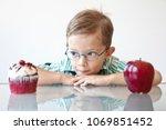 a little boy choosing between a ... | Shutterstock . vector #1069851452