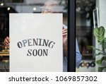 man putting on store opening... | Shutterstock . vector #1069857302