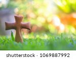 Small photo of Wooden Christian cross on green grass with nature background. Wooden Christian cross background. Wooden Christian cross wallpaper. Christianity Concept.