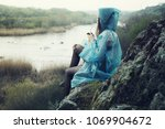 a lonely girl in a raincoat... | Shutterstock . vector #1069904672
