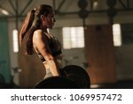 physically fit woman lifting... | Shutterstock . vector #1069957472