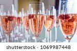 clear glasses of rose colored... | Shutterstock . vector #1069987448