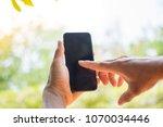 hand holding smart phone on... | Shutterstock . vector #1070034446