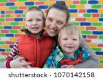 happy mother hugs her two... | Shutterstock . vector #1070142158