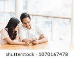 happy asian couple using... | Shutterstock . vector #1070167478