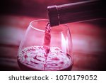 red wine is poured into a glass | Shutterstock . vector #1070179052