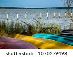 Ten brown pelicanons, each on their own post, with colorful canoes on the shore of Mobile Bay, at Fairhope Alabama