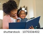 mother reading a book to her... | Shutterstock . vector #1070336402