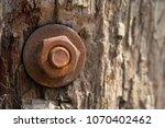 old rust nut on wooden pole ... | Shutterstock . vector #1070402462