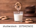cookie falls into the glass of ... | Shutterstock . vector #1070425652