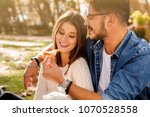couple at the park eating pizza | Shutterstock . vector #1070528558