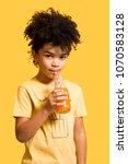 cute afro little boy drinking... | Shutterstock . vector #1070583128