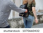 Small photo of thief in black and white jacket stealing the wallet or mobile phone from behind young caucasian woman traveling bag on street in big city, thief, crime, robber and steal concept