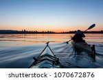 Small photo of Adventurous Girl Sea Kayaking during a vibrant winter sunrise with City Skyline in Background