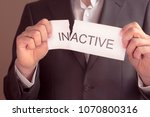 Small photo of inactive is active concept. Hand holding card with text inactive, tearing off word in. Conceptual image of changing position from inactive to active.