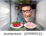 man choosing between fruits and ...   Shutterstock . vector #1070905112