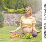 a pregnant woman sits on the...   Shutterstock . vector #1070966702