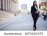 Small photo of Full lengt portrait of successful african american businesswoman dressed in formal wear posing and smiling at camera in downtown.Prosperous student of faculty of law standing near university building