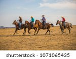 cowboys riding the open range | Shutterstock . vector #1071065435