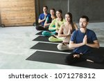 young women and men in yoga... | Shutterstock . vector #1071278312