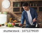 happy man cooking healthy food... | Shutterstock . vector #1071279035