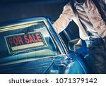 Men Putting For Sale Sign Under His Car Windshield. Selling Car Theme. - stock photo