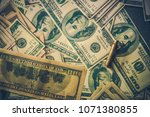 Pile of Dirty US Dollars Money. One Hundred Dollars Banknotes and Some Shell Casing on the Ground.  - stock photo