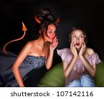 Small photo of Young woman sitting at home and seductive devil coming to her and giving a bad suggestion