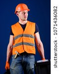 man in helmet  hard hat holds... | Shutterstock . vector #1071436082