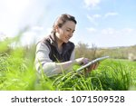 agronomist in crop field using... | Shutterstock . vector #1071509528
