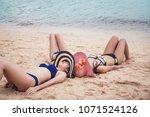 three women in bikini relaxing... | Shutterstock . vector #1071524126