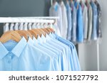 rack with clean clothes on... | Shutterstock . vector #1071527792
