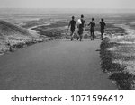 Small photo of The boys go off into the distance on the road, a black and white photo.