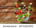 greek salad with flying... | Shutterstock . vector #1071622352