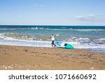 man carrying kayak at sea beach | Shutterstock . vector #1071660692